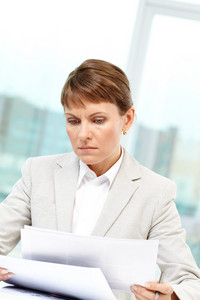 Photo of smart businesswoman working with papers in office
