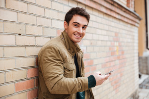 Photo of smiling young man walking on the street and chatting by his phone outdoors. Look at camera.
