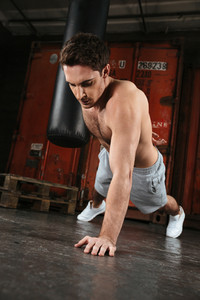 Photo of strong man make sport exercises in a gym. Looking down.