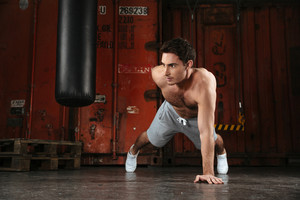 Photo of strong man make sport exercises. Looking aside.
