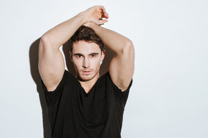 Photo of strong young man dressed in black t-shirt posing over white background looking at camera.