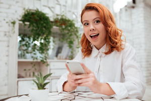Photo of surprised redhead young woman dressed in white shirt chatting by her phone while sitting in cafe. Looking at camera.