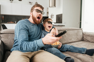 Photo of surprised young father holding remote control while watching TV with his little cute son using 3d glasses holding popcorn.