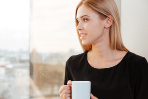 Photo of thoughtful happy woman worker standing in office holding cup of coffee. Look at window.