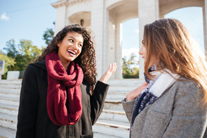 Photo of two gorgeous young women wearing scarfs communication. Against street background. Looking at each other.