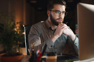 Photo of web designer dressed in shirt and wearing eyeglasses working late at night and looking at computer. Holding pen.