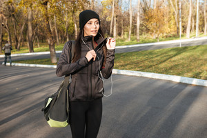 Photo of woman in warm clothes and earphones in autumn park holding bag. Look aside.