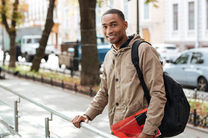 Photo of young african happy man wearing backpack standing in the street while holding book and looking at camera.