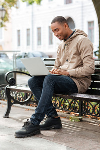 Photo of young african man with laptop sitting on a wooden bench and typing.