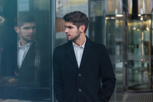 Photo of young attractive businessman standing near business center and look aside.