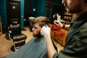 Photo of young bearded man getting haircut by hairdresser with electric razor while sitting in chair