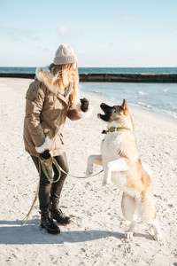 Photo of young beautiful caucasian lady walks in winter beach with dog on a leash.