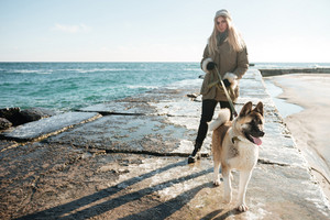 Photo of young beautiful lady walks in winter beach with dog on a leash.