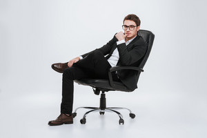Photo of young businessman sitting on chair at studio. Isolated over white background. Look at camera.