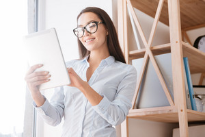 Photo of young businesswoman holding tablet and smiling. Look at tablet.