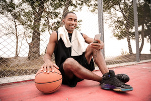 Photo of young cheerful african basketball player sitting in the park with towel touching basketball and chatting while listen to music. Looking at camera.
