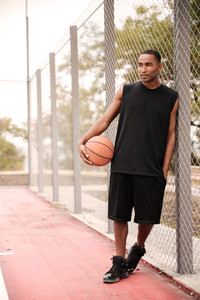 Photo of young cheerful african basketball player standing in the park while holding basketball. Look aside.