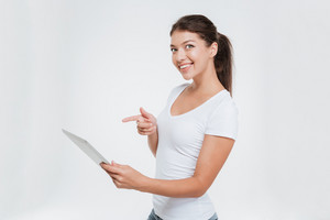 Photo of young cheerful woman holding digital tablet and pointing on it. Isolated on white background.
