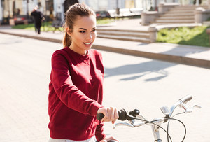 Photo of young cute girl dressed in sweater walking with her bicycle in the city. Look aside.