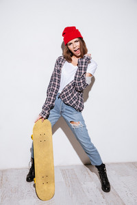 Photo of young emotional lady dressed in shirt in a cage print wearing hat standing isolated over white background holding skateboard