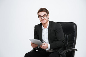 Photo of young handsome cheerful businessman sitting on chair at studio using tablet computer. Isolated over white background. Look at camera.