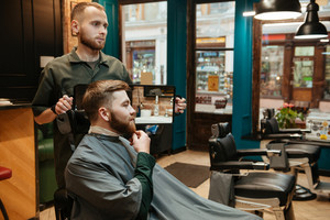 Photo of young handsome man getting beard haircut by hairdresser while sitting in chair at barbershop.