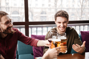 Photo of young happy friends sitting in cafe while drinking alcohol.