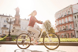 Photo of young happy girl dressed in sweater walking with her bicycle in the city.