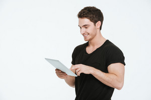 Photo of young happy man dressed in black t-shirt standing over white background using tablet computer.