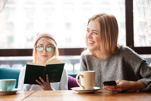 Photo of young happy two women friends sitting in cafe and reading book and drinking coffee while using phone.