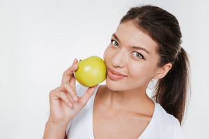Photo of young happy woman holding apple near face. Isolated on white background.