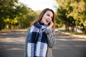 Photo of young happy woman wearing scarf talking on cellphone against nature background. Look aside.