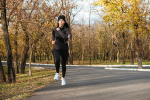 Photo of young lady runner in warm clothes and earphones running in autumn park