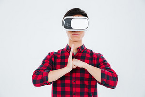Photo of young man dressed in casual shirt in a cage and wearing virtual reality device make karate gesture with fist in palm. Isolated over white background.