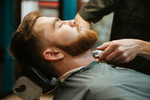 Photo of young man getting beard haircut by hairdresser while lies in chair at barbershop.
