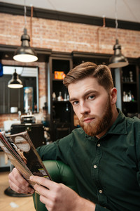 Photo of young man sitting in armchair at barbershop and reading magazine. Looking at camera.