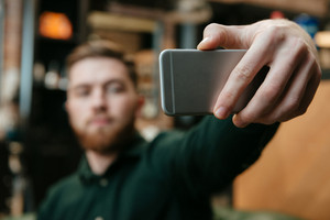 Photo of young man sitting in armchair at barbershop and take a selfie. Focus on phone.