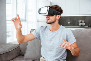 Photo of young man wearing virtual reality device while sitting on sofa