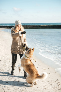 Photo of young playful lady walks in winter beach with dog on a leash.