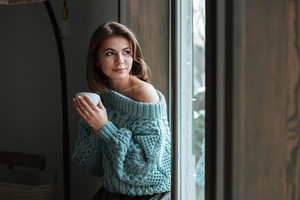 Photo of young pretty cute woman look at window in cafe and drinking coffee.