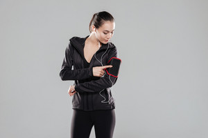 Photo of young pretty fitness lady standing over grey background listening music with earphones.