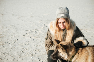 Photo of young pretty woman walks in winter beach with dog on a leash.