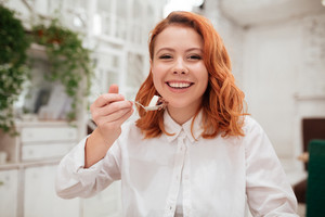 Photo of young redhead pretty woman eating cake in cafe. Looking at the camera.
