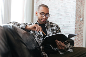 Photo of young serious african businessman sitting on sofa in office holding folder and pencil. Look at folder.