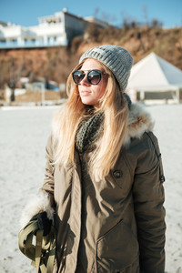Photo of young serious woman wearing sunglasses walks in winter beach with dog on a leash.