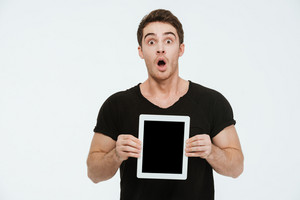 Photo of young shocked man dressed in black t-shirt standing over white background showing display of tablet computer.