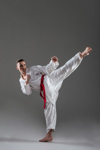 Photo of young sportsman dressed in kimono practice in karate isolated over grey background. Looking aside.