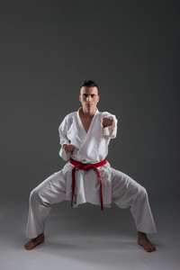 Photo of young sportsman dressed in kimono practice in karate isolated over grey background. Looking at camera.