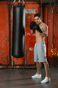 Photo of young strong boxer posing in a gym with punchbag. Looking at camera.