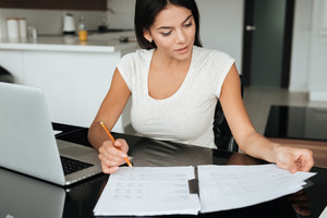 Photo of young woman analyzing home finances with laptop while looking at documents.